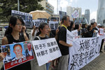 Activists from various groups including parents and religious hold placards of picture of police commander with Chinese reads
