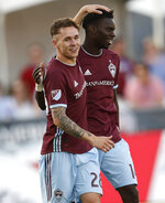 Colorado Rapids midfielder Sam Nicholson, front, congratulates forward Dominique Badji for his goal against the Chicago Fire during the first half of an MLS soccer match Wednesday, June 13, 2018, in Commerce City, Colo. (AP Photo/David Zalubowski)