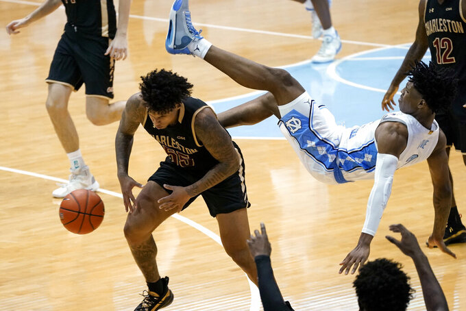 North Carolina guard Caleb Love falls over the back of College of Charleston guard Brevin Galloway (55) during the second half of an NCAA college basketball game in Chapel Hill, N.C., Wednesday, Nov. 25, 2020. (AP Photo/Gerry Broome)