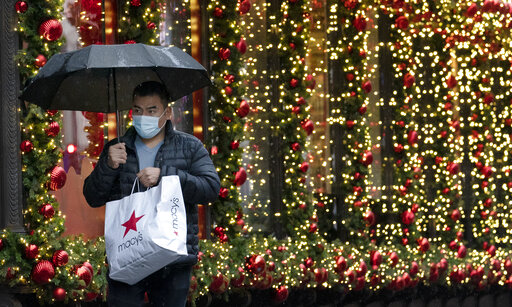 FILE - In this Nov. 30, 2020 file photo, a shopper walks by a holiday window display in New York. Factoring holiday expenses into your budget all year long is effective for avoiding debt, but it's not always feasible with a limited budget or unforeseen expenses. When that's the case, lacking a strategy for holiday spending can leave you vulnerable to debt and overspending that delays financial goals. But it's not too late to come up with a last-minute plan to save money for the holidays. (AP Photo/Mark Lennihan, File)