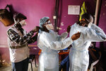 Medical staff aid each other to put on protective equipment as a precaution before dealing with patients with non-coronavirus related issues at the Medecins Sans Frontieres (Doctors without Borders) clinic in the Mathare slum, or informal settlement, of Nairobi, Kenya Thursday, May 28, 2020. According to MSF, measures being taken to curb the spread of the coronavirus such as a nightly curfew and transport restrictions, shortages of protective equipment, and the risk of contamination, are causing disruption to the provision of general health services in the low-income neighborhood. Some of these include the closure of private clinics and an unwillingness by others to admit patients with respiratory issues caused by tuberculosis, asthma or pneumonia. (AP Photo/Brian Inganga)