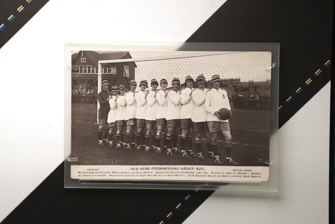 A photograph showing Lily Parr, at right holding the ball, is displayed at an exhibition at the National Football Museum in Manchester, England, Thursday, July 29, 2021. Lily Parr, whose record-setting career was overlooked when the bosses of English soccer shunned the women's game, is now the focus of a new permanent exhibition at the National Football Museum in Manchester. (AP Photo/Jon Super)