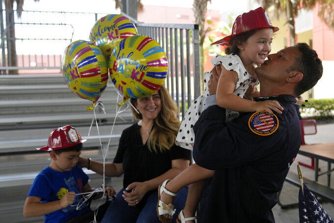 Capt. Eric Hernandez lifts up his daughter Isabella, 3, as his wife Yaimara and son Eric, 4, look on, as members of Miami-Dade Fire Rescue's urban search and rescue team are reunited with their families after weeks of working on the rubble pile at the collapsed Champlain Towers South condominium, on Friday, July 23, 2021, in Doral, Fla. (AP Photo/Rebecca Blackwell)