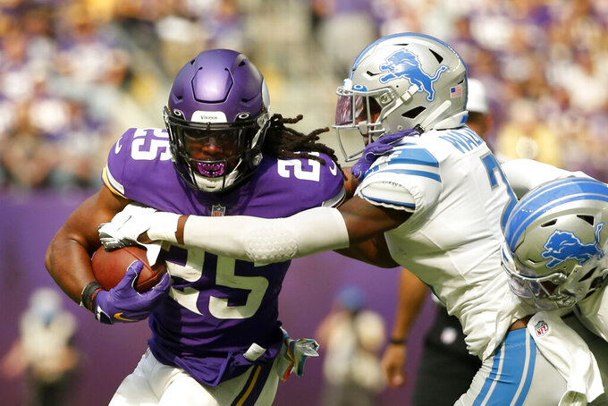 Minnesota Vikings running back Alexander Mattison (25) tries to break a tackle by Detroit Lions free safety Tracy Walker III (21) during the first half of an NFL football game, Sunday, Oct. 10, 2021, in Minneapolis. (AP Photo/Bruce Kluckhohn)
