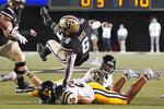 Vanderbilt running back Re'Mahn Davis (6) falls over East Tennessee State defensive back Alijah Huzzie (28) in the first half of an NCAA college football game Saturday, Sept. 4, 2021, in Nashville, Tenn. (AP Photo/Mark Humphrey)