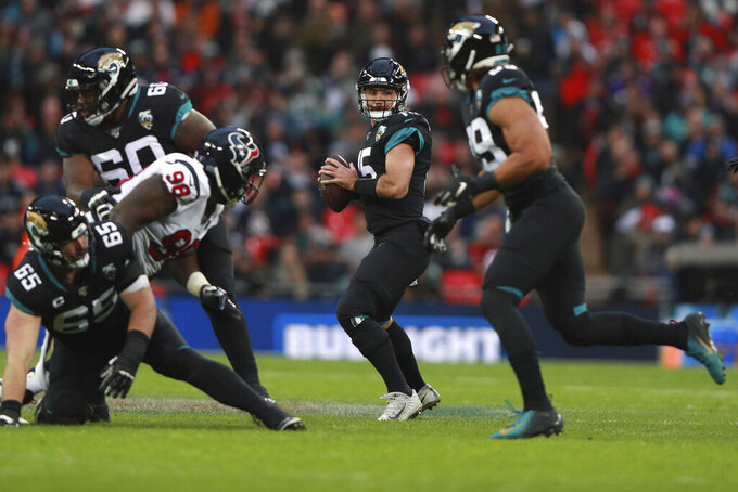 Jacksonville Jaguars quarterback Gardner Minshew (15) works in the pocket against the Houston Texans during the second half of an NFL football game at Wembley Stadium, Sunday, Nov. 3, 2019, in London. (AP Photo/Ian Walton)