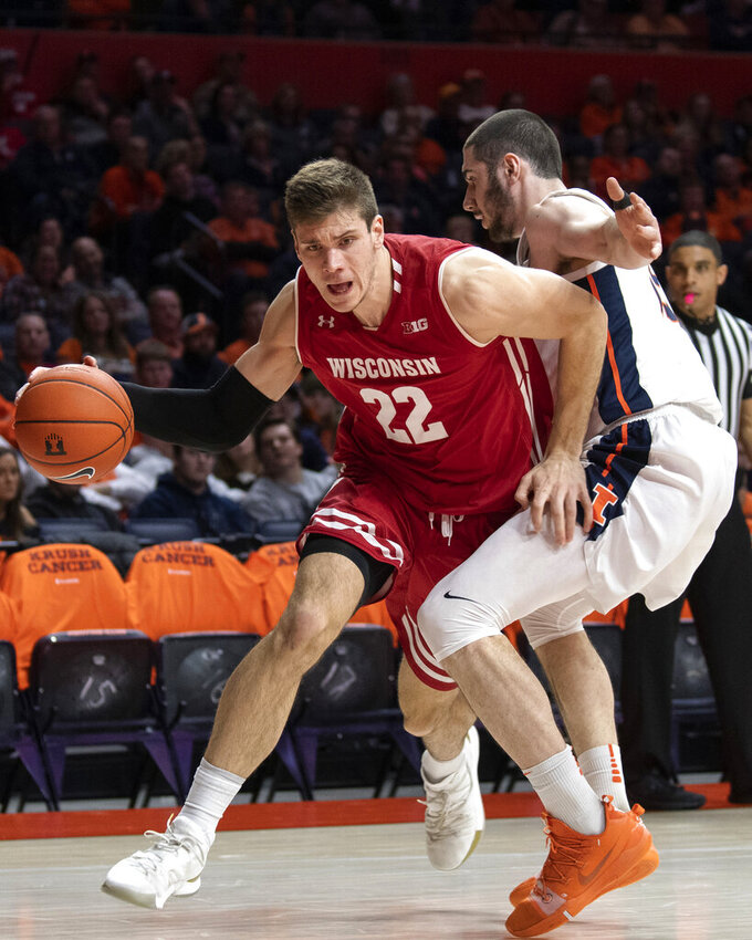 Wisconsin forward Ethan Happ (22) drives to the basket past Illinois forward Giorgi Bezhanishvili (15) during the second half of an NCAA college basketball game in Champaign, Ill., Wednesday, Jan. 23, 2019. (AP Photo/Stephen Haas)