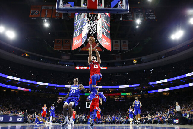 Philadelphia 76ers' Ben Simmons (25) goes up for a shot past Los Angeles Clippers' Lou Williams (23) during the first half of an NBA basketball game, Tuesday, Feb. 11, 2020, in Philadelphia. (AP Photo/Matt Slocum)