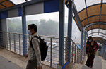 In this Sunday, Nov. 3, 2019, photo, Indians wear pollution mask and cross over a pedestrian bridge amidst thick layer of smog in New Delhi, India. Authorities in New Delhi are restricting the use of private vehicles on the roads under an