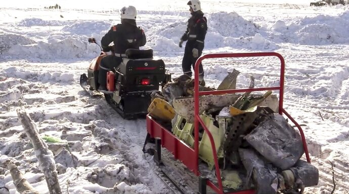 In this photo provided by the Russian Emergency Situations Ministry, emergency personnel carry wreckage of an AN-148 plane crash in Stepanovskoye village, about 40 kilometers (25 miles) from the Domodedovo airport, Russia, Tuesday, Feb. 13, 2018. EInvestigators are studying the information from flight recorders of a Russian passenger plane that has crashed near Moscow killing all 71 people on board. The Moscow-based Interstate Aviation Committee said Tuesday its experts managed to recover the data from both the plane's flight data and cockpit conversation recorders. (Russian Ministry for Emergency Situations photo via AP)