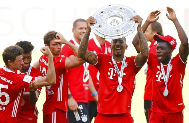 FILE - In this June 27, 2020, file photo, Munich's Jerome Boateng lifts the trophy after the German Bundesliga soccer match between VfL Wolfsburg and FC Bayern Munich in Wolfsburg, Germany. Boateng has talked to teammates about the pain of facing racist abuse. (Kai Pfaffenbach/Pool Photo via AP, File)
