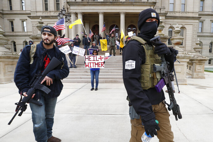 FILE - In this April 15, 2020 file photo, protesters carry rifles near the steps of the Michigan State Capitol building in Lansing, Mich.  A plot to kidnap Michigan's governor has put a focus on the security of governors who have faced protests and threats over their handling of the coronavirus pandemic. The threats have come from people who oppose business closures and restrictions on social gatherings. (AP Photo/Paul Sancya File)