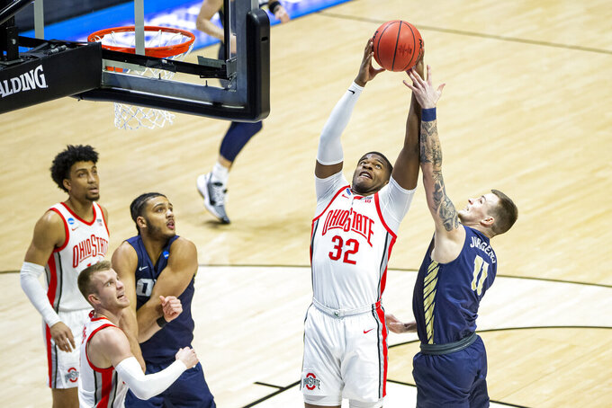 Ohio State's E.J. Liddell (32) grabs a rebound over Oral Roberts' Carlos Jürgens (11) during the first half of a first round game in the NCAA men's college basketball tournament, Friday, March 19, 2021, at Mackey Arena in West Lafayette, Ind. (AP Photo/Robert Franklin)