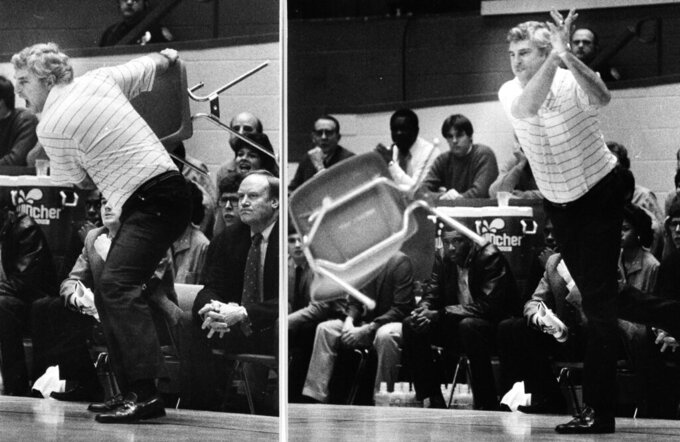 FILE - This Feb. 23, 1985, file photo shows Indiana coach Bob Knight winding up and pitching a chair across the floor during Indiana's 72-63 loss to Purdue, in Bloomington, Ind. Tony Hinkle turned Butler's pass-and-cut offense of the 1920s into a coaching textbook for generations. Bob Knight and Gene Keady added their own revisions following Hinkle's forced retirement in 1970. Today, those three remain the gold standard of basketball innovation in Indiana, a state where successful coaches have spent more than a century testing novel concepts, breaking barriers and polishing philosophies before introducing them America.(AP Photo/File)
