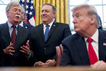 FILE - In this Feb. 7, 2019 file photo, from left, National Security Adviser John Bolton, accompanied by Secretary of State Mike Pompeo, and President Donald Trump, speaks before Trump signs a National Security Presidential Memorandum to launch the