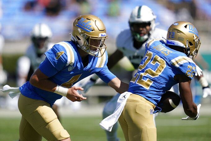 UCLA quarterback Ethan Garbers (4) hands off to running back Keegan Jones (22) during the second half of an NCAA college football game against Hawaii Saturday, Aug. 28, 2021, in Pasadena, Calif. (AP Photo/Ashley Landis)