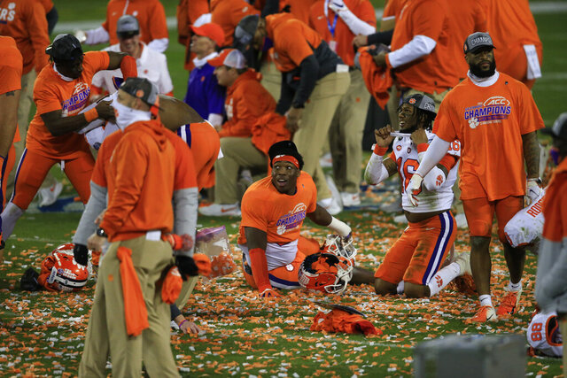 Clemson players celebrate following their 34-10 victory over Notre Dame at the Atlantic Coast Conference championship NCAA college football game, Saturday, Dec. 19, 2020, in Charlotte, N.C. (AP Photo/Brian Blanco)