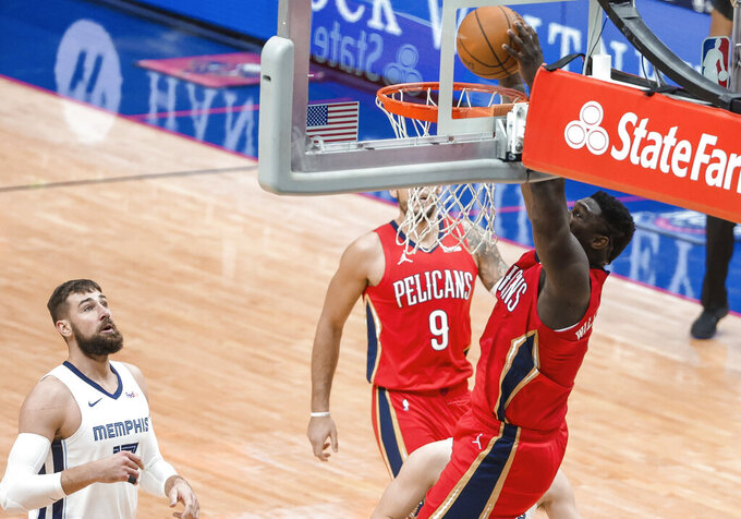 New Orleans Pelicans forward Zion Williamson (1) dunks as Memphis Grizzlies center Jonas Valanciunas (17) watches during the first quarter of an NBA basketball game in New Orleans, Saturday, Feb. 6, 2021. (AP Photo/Derick Hingle)