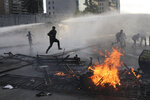 FILE - In this Oct. 29, 2019, file photo, anti-government protesters run from police spraying water cannons where a street barricade burns, set by demonstrators, in Santiago, Chile. From Honduras to Chile, popular frustration with anemic economic growth, entrenched corruption and gaping inequality is driving the region's middle classes to rebel against incumbents of all ideological bents in what has been dubbed by some the Latin American Spring. (AP Photo/Rodrigo Abd, File)