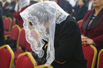 In this Jan. 20, 2019 photo, a woman prays during  Sunday service at Mart Shmony Orthodox Church the northern town of Irbil, Iraq. Two years after it was liberated from Islamic State militants, only a fraction of Christian residents have returned to Bartella. Many fear intimidation by the town's population of Shabak, a Shiite Muslim ethnic group who dominate the militias that now run Bartella. Most now live in Ankawa, the Christian neighborhood of Irbil. (AP Photo/Fay Abuelgasim)
