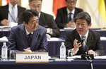 FILE - In this  Jan. 19, 2019, file photo, Japan's Prime Minister Shinzo Abe, left, and Minister of Economy, Trade, and Industry Toshimitsu Motegi, right, share a light moment during an opening session of the Comprehensive and Progressive Trans-Pacific Partnership (CPTPP) in Tokyo. Motegi said Friday, May 17, 2019 Washington won't be demanding any numerical restrictions on Japanese auto exports to the U.S., speculated by media reports as a possibility. (AP Photo/Eugene Hoshiko, File)