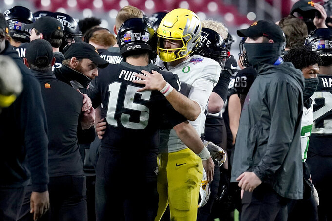 Iowa State quarterback Brock Purdy (15) hugs Oregon quarterback Tyler Shough after the Fiesta Bowl NCAA college football game against Oregon, Saturday, Jan. 2, 2021, in Glendale, Ariz. Iowa State won 34-17. (AP Photo/Ross D. Franklin)