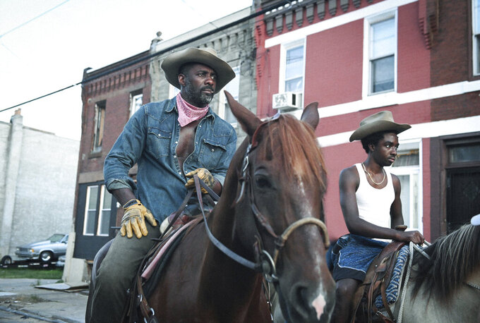"""This image provided by Netflix shows Idris Elba, left, and Caleb McLaughlin in a scene from the film """"Concrete Cowboy,"""" premiering April 2 on Netflix. (Netflix via AP)"""