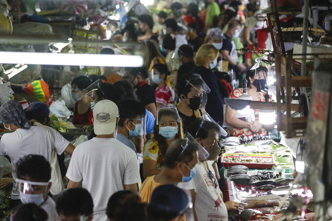 Poeple wearing face masks and face shields to prevent the spread of the coronavirus buy food at the Munoz market in Quezon city, Philippines as they prepare for a stricter lockdown on Sunday March 28, 2021. The government will start stricter lockdown measures next week as the country struggles to control an alarming surge in COVID-19 cases. (AP Photo/Aaron Favila)