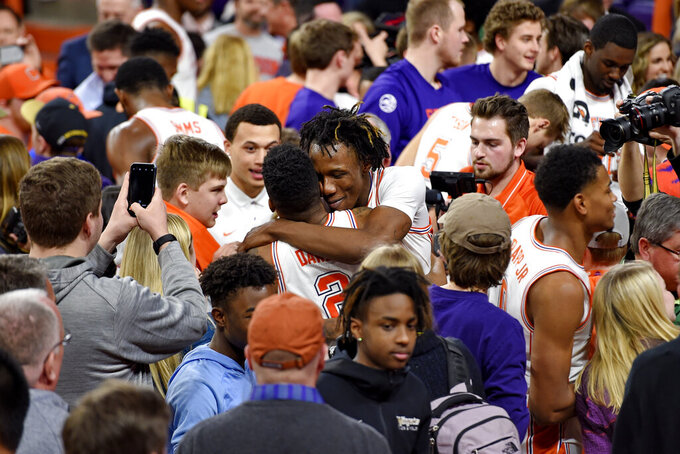 Clemson's Tevin Mack, center back, hugs Al-Amir Dawes, who hit the winning shot, while fans and players celebrate after an NCAA college basketball game against Florida State Saturday, Feb. 29, 2020, in Clemson, S.C. Clemson won 70-69. (AP Photo/Richard Shiro)