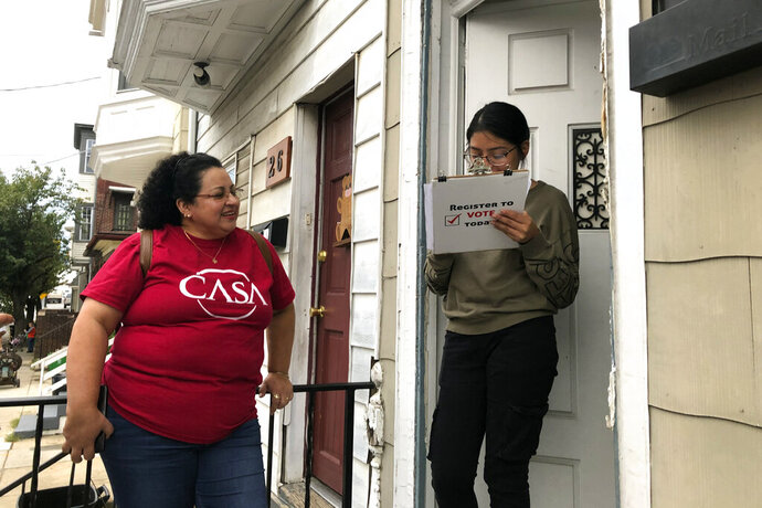 Mirna Orellana, left, a community organizer from the non-profit group We Are Casa, helps Karyme Navarro, right, fill out a voter registration form in York, Pa., on Sept. 30, 2019. Democrats are counting on Hispanics so enraged by President Donald Trump's anti-immigrant rhetoric that they'll turn out in force to deny him a second term, but Trump's reelection campaign has launched its own Hispanic outreach efforts in non-traditional places like Pennsylvania, arguing that even slim gains could decide the 2020 race. (AP Photo/Will Weissert)