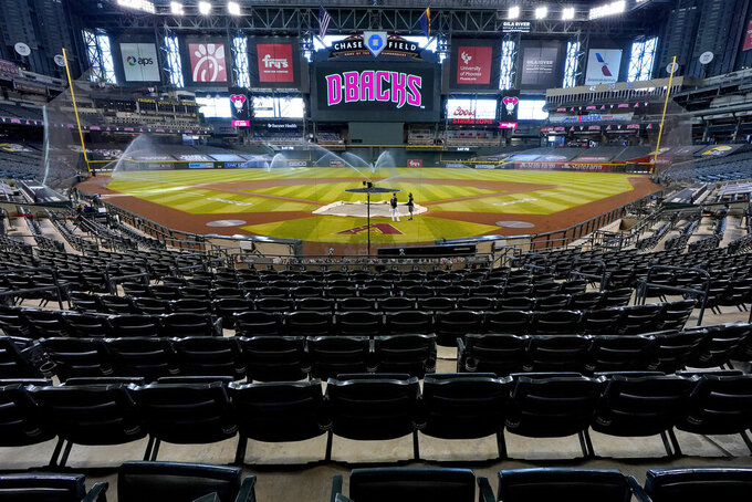 FILE - Chase Field sits empty after the Colorado Rockies decided not to play their baseball game against the Arizona Diamondbacks, on Aug. 27, 2020, in Phoenix. Arizona's first sports betting operations are set to open in time for the start of the NFL season with live wagers allowed on college and professional sports. Betting will be allowed starting Thursday, Sept. 9, 2021, online and at the FanDuel Sportsbook at the downtown Phoenix arena where the Phoenix Suns play and at temporary betting windows at the Arizona Diamondbacks' Chase Field. (AP Photo/Matt York, File)