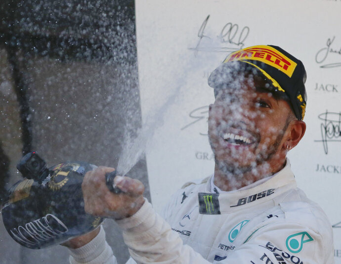 Mercedes driver Lewis Hamilton of Britain sprays champagne on the podium after winning the Spanish Formula One Grand Prix at the Barcelona Catalunya racetrack in Montmelo, Spain, Sunday, May 13, 2018. (AP Photo/Emilio Morenatti)