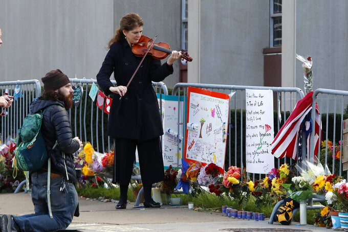 Monique Mead plays her violin on the sidewalk outside the Tree of Life synagogue in Pittsburgh on Sunday, Oct. 27, 2019, the first anniversary of the shooting at the synagogue that killed 11 worshippers. (AP Photo/Gene J. Puskar)