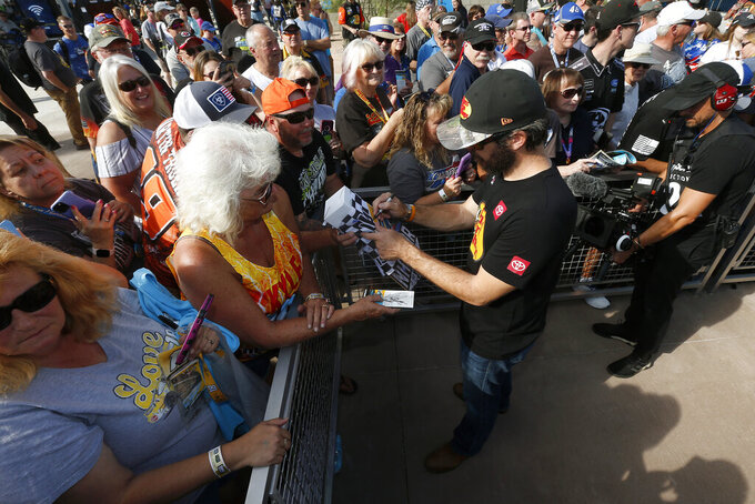 Driver Martin Truex Jr. signs autographs for fans prior to the NASCAR Cup Series auto race at ISM Raceway, Sunday, Nov. 10, 2019, in Avondale, Ariz. (AP Photo/Ralph Freso)