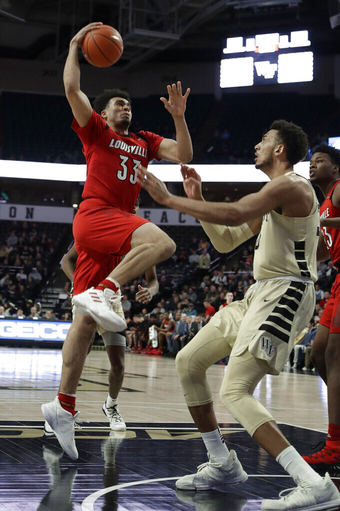 Louisville's Jordan Nwora (33) goes up to the basket as Wake Forest's Olivier Sarr defends during the first half of an NCAA college basketball game in Winston-Salem, N.C., Wednesday, Jan. 30, 2019. (AP Photo/Chuck Burton)