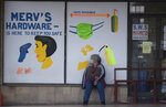 A woman wearing a surgical face mask to protect against coronavirus, sits outside a hardware shop in Johannesburg, South Africa, Monday, Aug. 31, 2020. (AP Photo/Themba Hadebe)