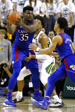 Kansas center Udoka Azubuike, left, looks to hand the ball to guard Devon Dotson, right, against Baylor during the second half of an NCAA college basketball game on Saturday, Feb. 22, 2020, in Waco, Texas. (AP Photo/Ray Carlin)