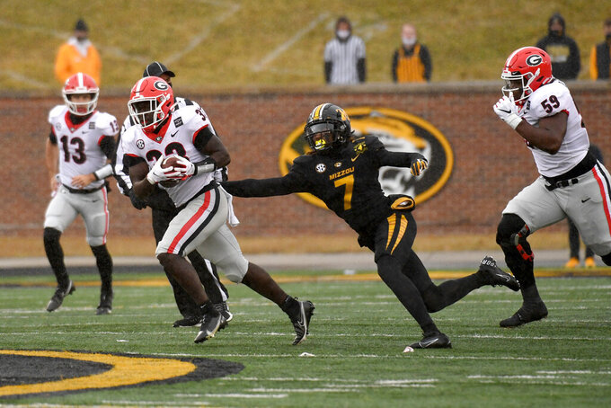 Georgia running back Daijun Edwards (33) slips past Missouri defensive back Stacy Brown (7) during the second half of an NCAA college football game Saturday, Dec. 12, 2020, in Columbia, Mo. Georgia won 49-14. (AP Photo/L.G. Patterson)