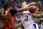 Kansas guard Christian Braun (2) is fouled by Texas Tech forward TJ Holyfield (22) during the first half of an NCAA college basketball game in Lawrence, Kan., Saturday, Feb. 1, 2020. (AP Photo/Orlin Wagner)