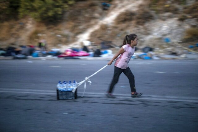 A migrant pulls a crate with bottles of water on the northeastern island of Lesbos, Greece, Friday, Sept. 18, 2020. Police on the Greek island of Lesbos resumed an operation Friday to move migrants made homeless by fires to new camp amid a local COVID-19 outbreak. It came a day after 5,000 people were taken to the army-built camp, 135 testing positive for the new coronavirus. (AP Photo/Petros Giannakouris)