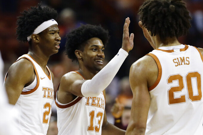 Texas guard Jase Febres (13) celebrates a score with teammate Jericho Sims (20) during the second half of an NCAA college basketball game against Central Michigan, Saturday, Dec. 14, 2019, in Austin, Texas. (AP Photo/Eric Gay)