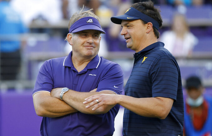 TCU head coach Gary Patterson, left, and West Virginia head coach Neal Brown talk on the playing field before an NCAA college football game Saturday, Oct. 23, 2021, in Fort Worth, Texas. (AP Photo/Ron Jenkins)