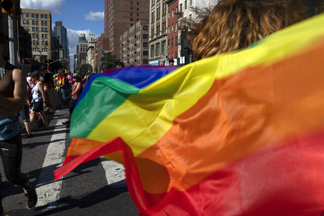 FILE - In this June 30, 2019, file photo parade-goers carrying rainbow flags walk down a street during the LBGTQ Pride march in New York, to celebrate five decades of LGBTQ pride, marking the 50th anniversary of the police raid that sparked the modern-day gay rights movement. Democrats flooded Twitter and email inboxes this week with praise for the watershed Supreme Court decision shielding gay, lesbian and transgender people from job discrimination.  (AP Photo/Wong Maye-E, File)