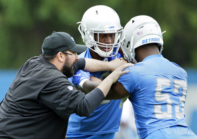 FILE - In this June 6, 2019, file photo, Detroit Lions coach Matt Patricia, left, works with linebackers Tre Lamar, center, and Malik Carney (53) during NFL football training camp in Allen Park, Mich. NFL general managers and coaches, and those who assist them, work within a highly competitive culture. Putting in extremely long hours is simply understood as part of the job. For the past few months, though, Patricia's wife and kids have had unprecedented access to him. (AP Photo/Duane Burleson, File)