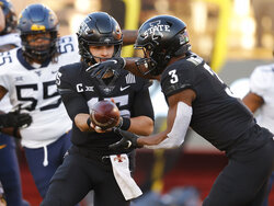 Iowa State quarterback Brock Purdy, left, hands off to Iowa State running back Kene Nwangwu during the first half of an NCAA college football game against West Virginia, Saturday, Dec. 5, 2020, in Ames, Iowa. (AP Photo/Matthew Putney)