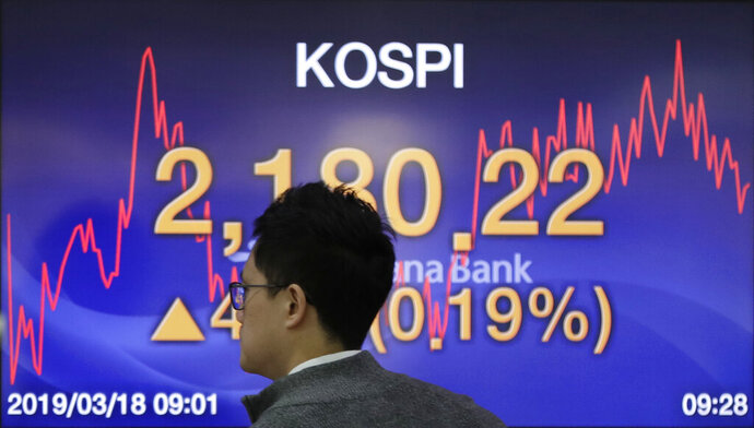 A currency trader walks by the screen showing the Korea Composite Stock Price Index (KOSPI) at the foreign exchange dealing room in Seoul, South Korea, Monday, March 18, 2019. Asian shares were mixed Monday as investors continued to watch for signs the U.S. and China could be making progress on critical negotiations aimed at resolving a trade war between the world's two biggest economies. (AP Photo/Lee Jin-man)