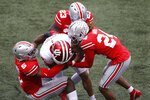 Ohio State defenders, left to right, Baron Browning, Marcus Hooker, and Shaun Wade tackle Indiana receiver Ty Fryfogle during the first half of an NCAA college football game Saturday, Nov. 21, 2020, in Columbus, Ohio. (AP Photo/Jay LaPrete)
