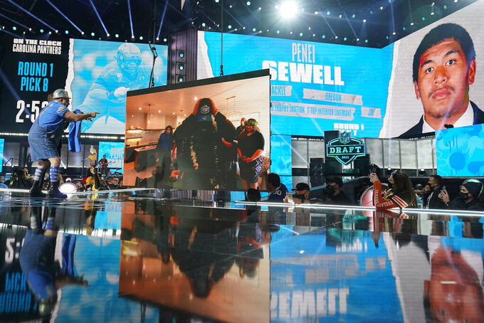 A Detroit Lions fan, left, who was chosen to be on stage, points to an image of the team's first-round pick Penei Sewell, an offensive lineman from Oregon, on the display on stage at the NFL football draft, Thursday April 29, 2021, in Cleveland. (AP Photo/Tony Dejak)
