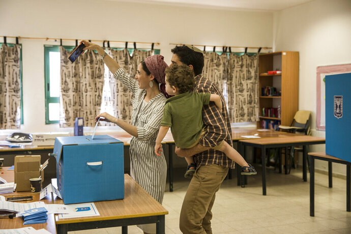 A family votes in the settlement of Tekoa, West Bank, Tuesday, Sept. 17, 2019. Israelis began voting Tuesday in an unprecedented repeat election that will decide whether longtime Prime Minister Benjamin Netanyahu stays in power despite a looming indictment on corruption charges. (AP Photo/Tsafrir Abayov)