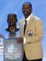 Former NFL player Ty Law poses with a bust of himself during the induction ceremony at the Pro Football Hall of Fame, Saturday, Aug. 3, 2019, in Canton, Ohio. (AP Photo/Ron Schwane)